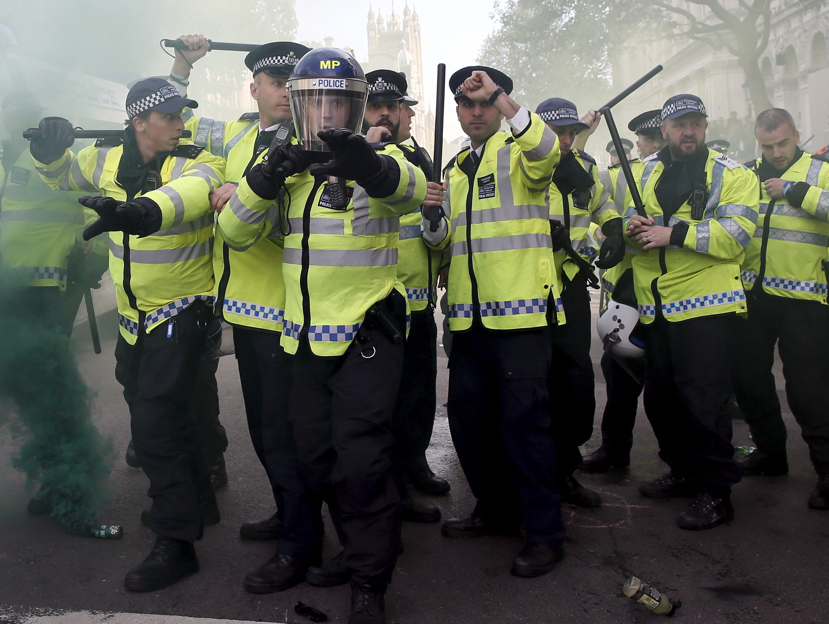 Police officers raise their batons as a smoke bomb goes off during a protest in central London. Picture: Reuters/Stefan Wermuth