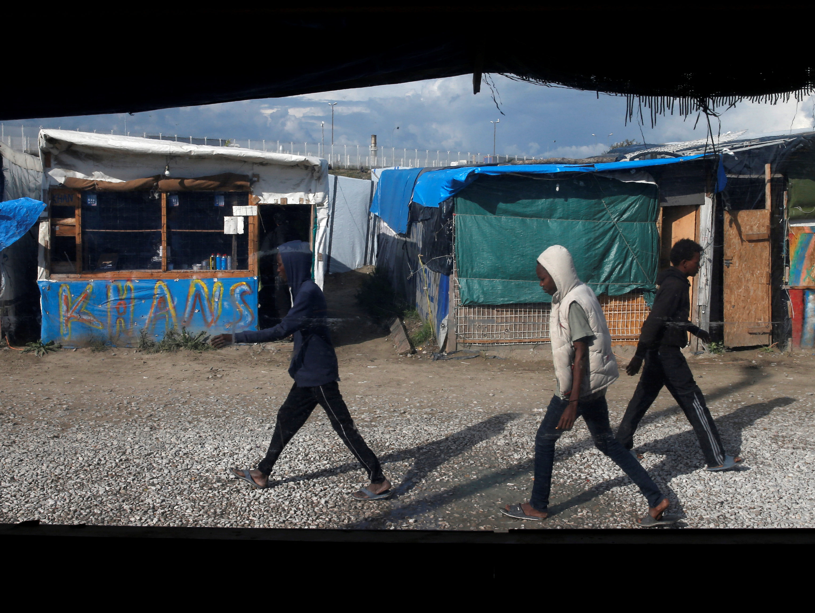 """Migrants are seen through the window of a makeshift Afghan restaurant as they walk in the northern area of the camp called the """"Jungle"""" in Calais, France, October 1, 2016. Picture: Reuters"""