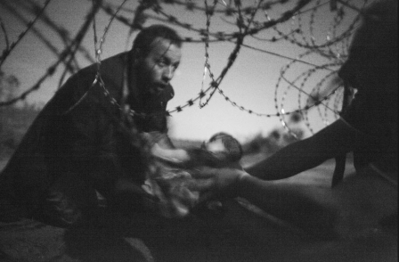 Image of baby being passed through razorwire fence into European Union wins World Press Photo prize